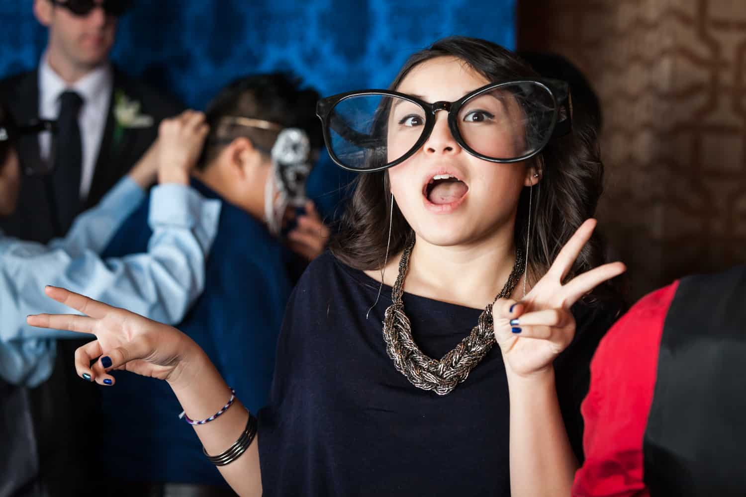 Young girl wearing oversized glasses at photobooth at a Lighthouse at Chelsea Piers wedding