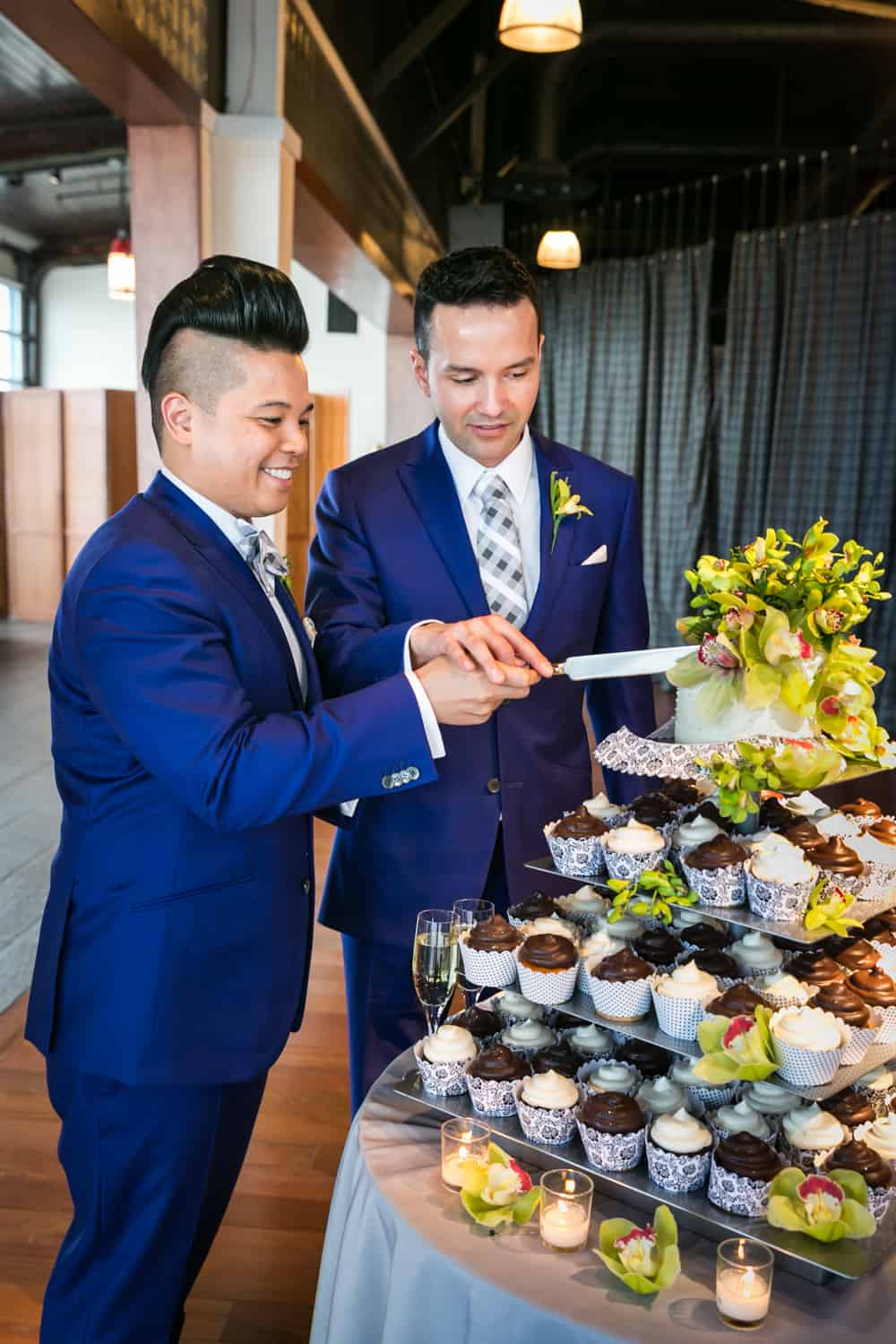 Two grooms cutting cake at a Lighthouse at Chelsea Piers wedding