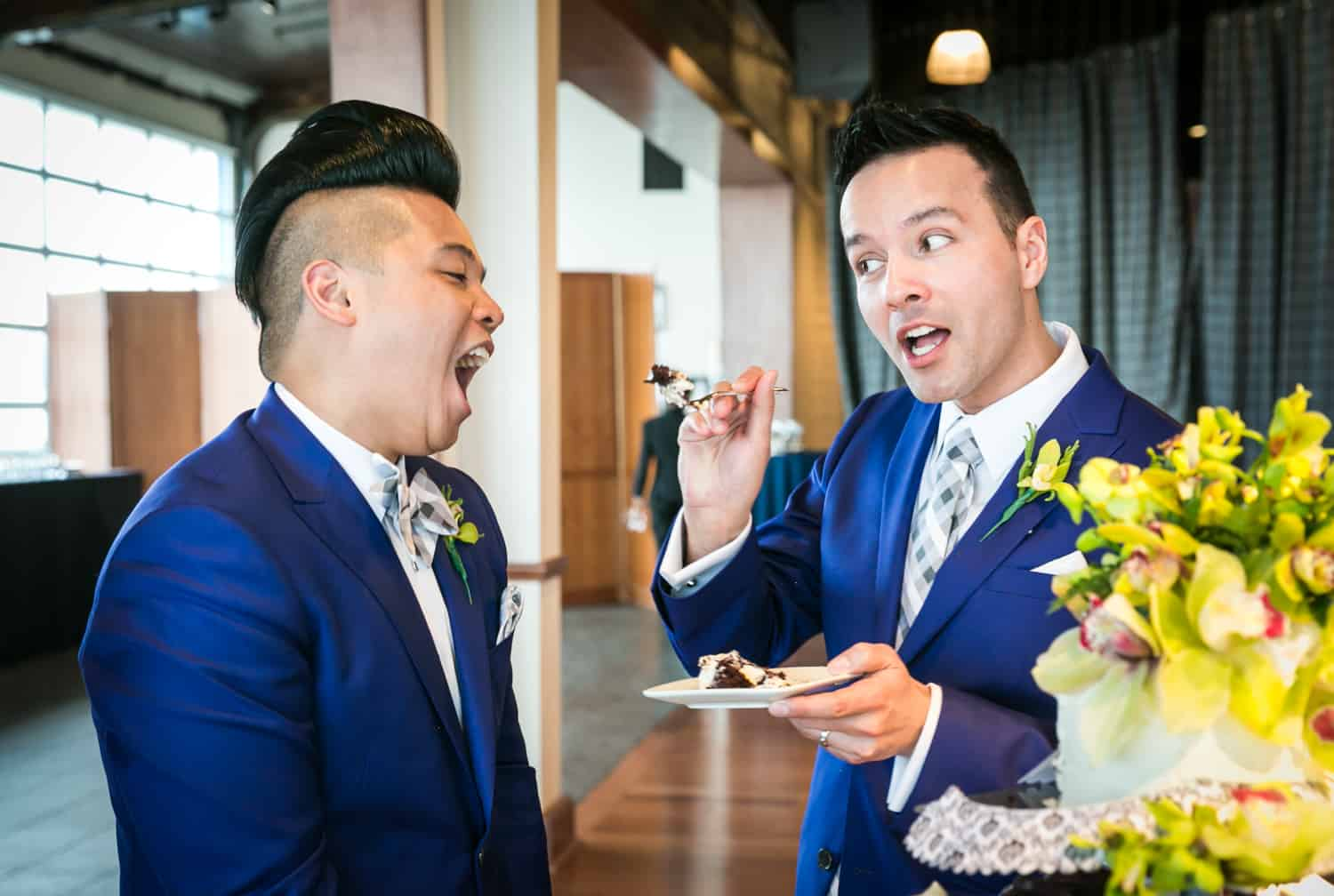 Groom about to feed cake to another groom at a Lighthouse at Chelsea Piers wedding