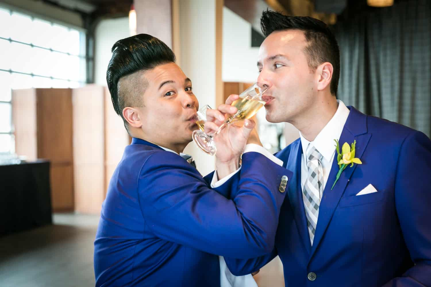 Two grooms drinking champagne through entwined arms
