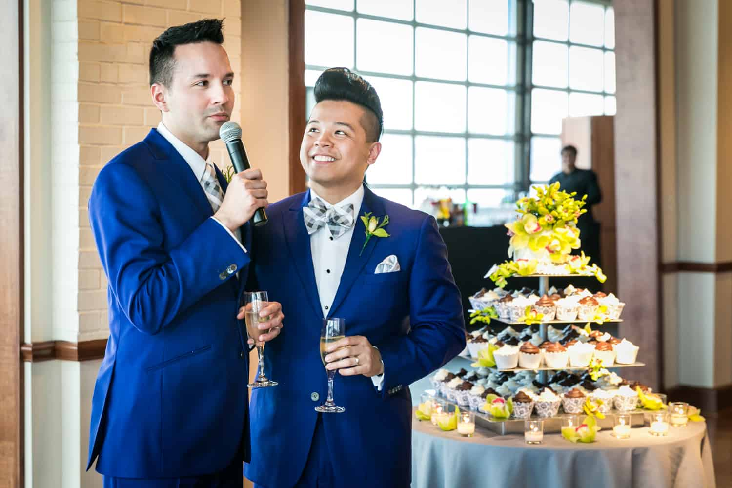 Two grooms making a speech beside tier of cupcakes