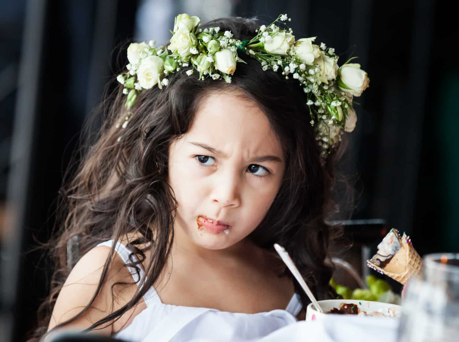 Flower girl with chocolate over her mouth wearing flower crown