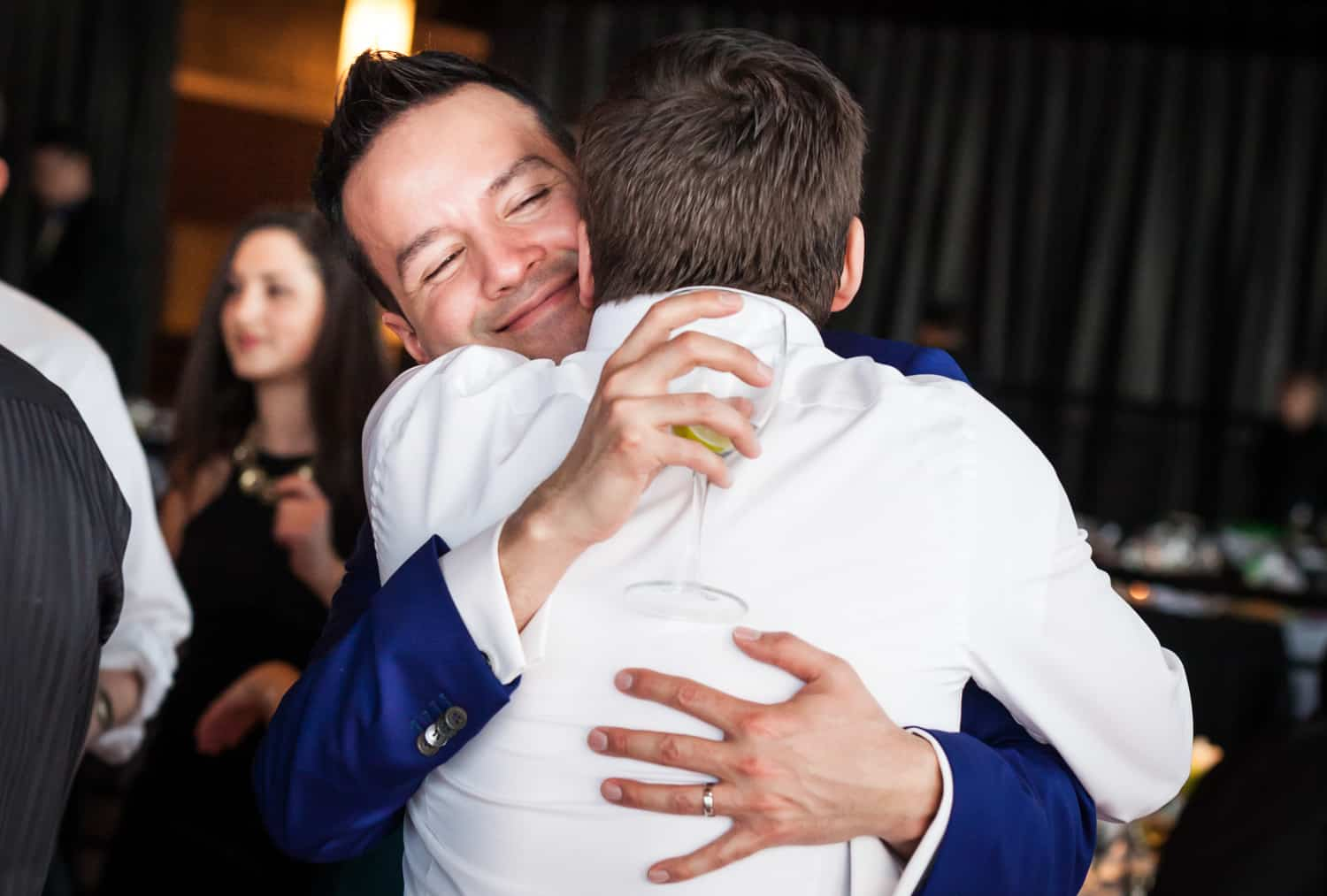 Groom hugging guest at a Lighthouse at Chelsea Piers wedding