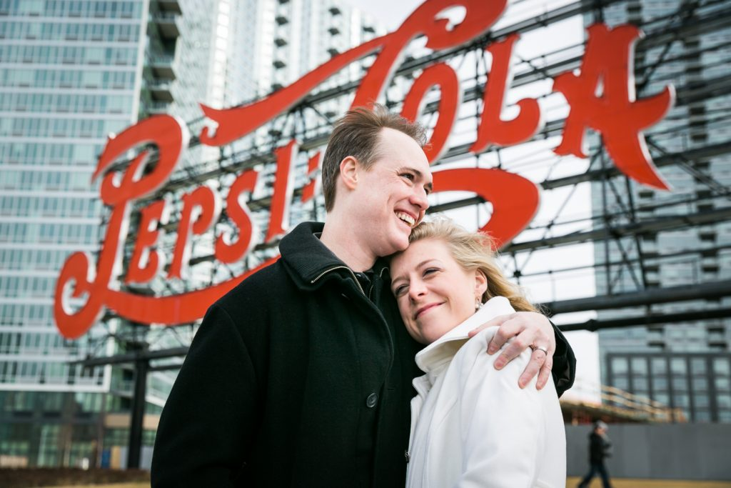 Couple hugging in front of neon Pepsi Cola sign in Gantry Plaza State Park at a Long Island City wedding brunch