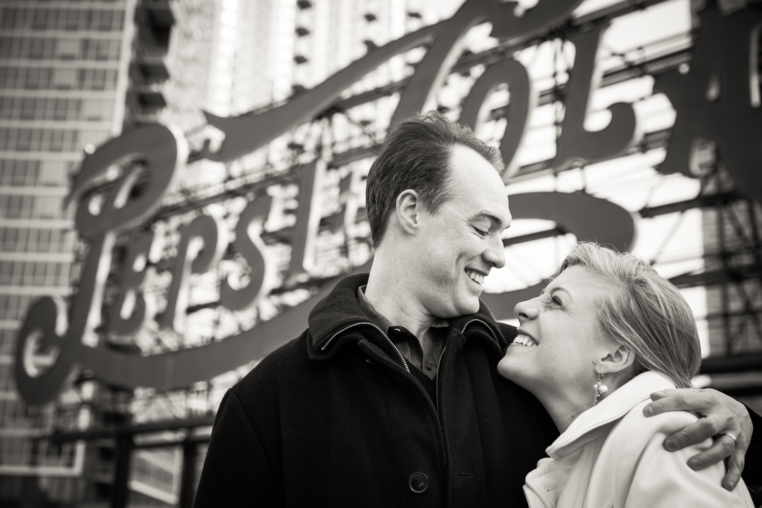 Black and white photo of couple in front of Pepsi Cola sign in Gantry Plaza State Park