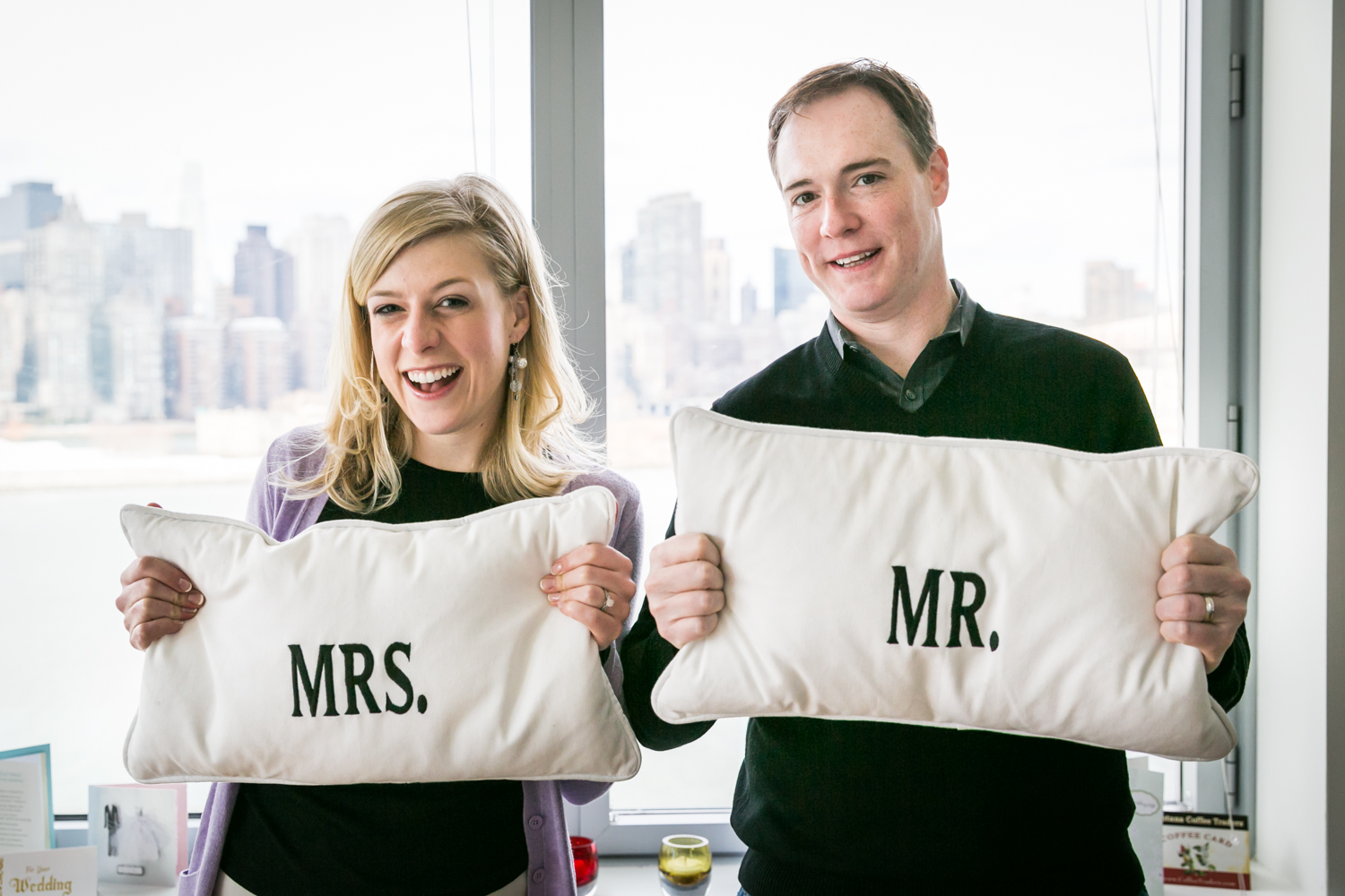 Bride and groom holding Mr. and Mrs. pillows at a Long Island City wedding brunch