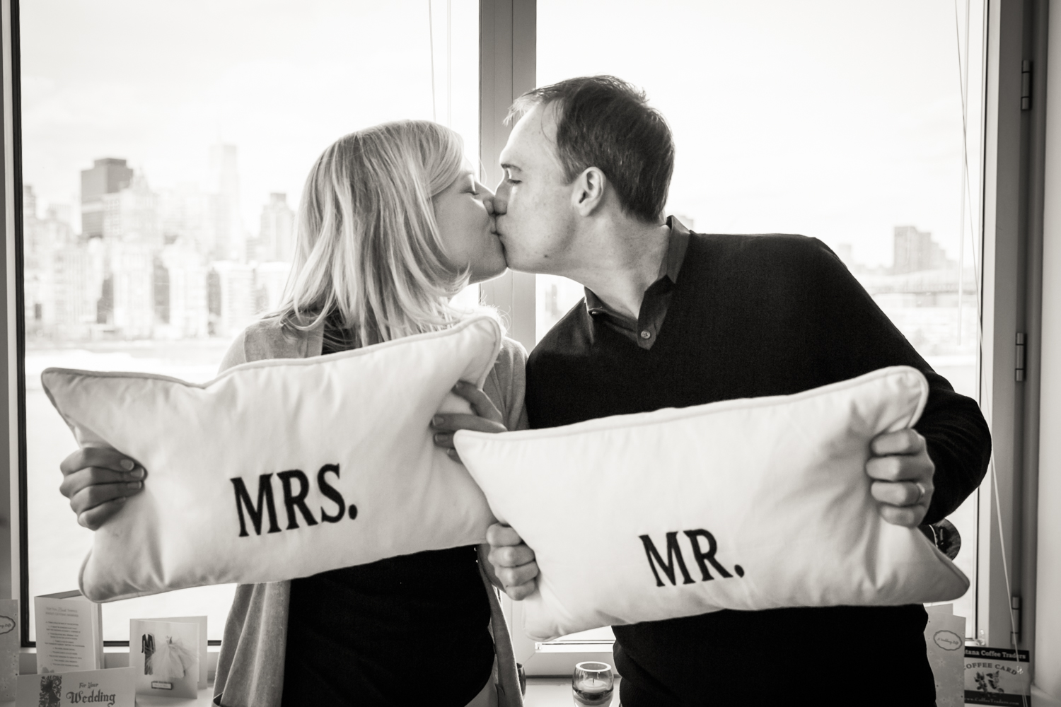Black and white photo of bride and groom kissing over Mr. and Mrs. pillows