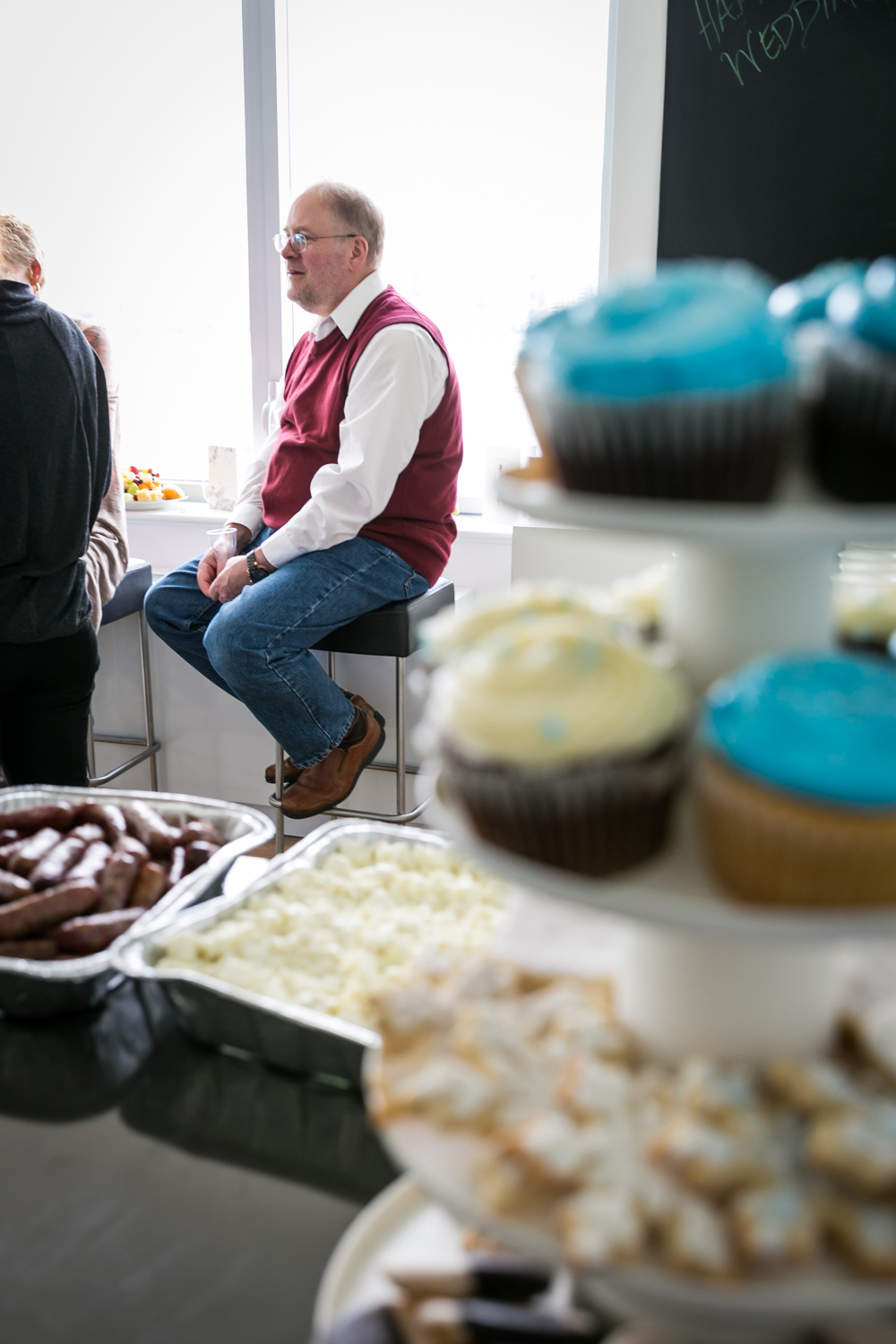 View through cupcakes of man sitting by window