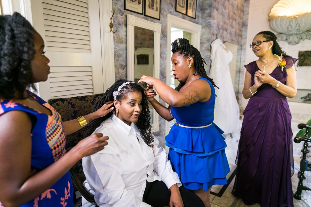 Mother watching while bridesmaids help bride with braided hair