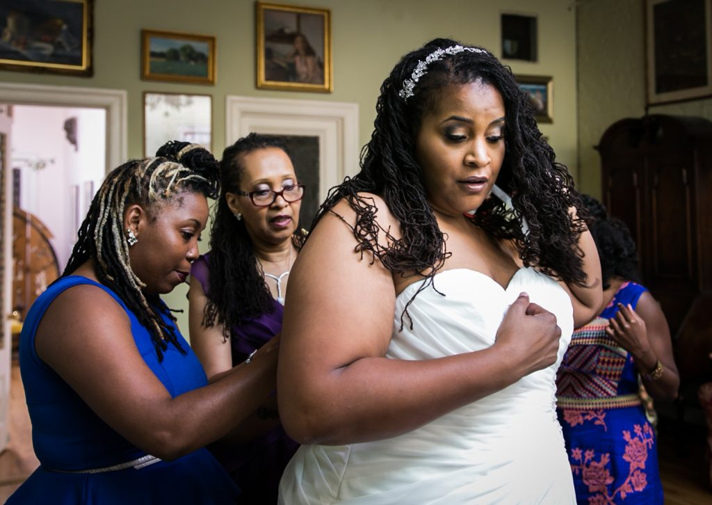 Mother and bridesmaid helping bride get into dress