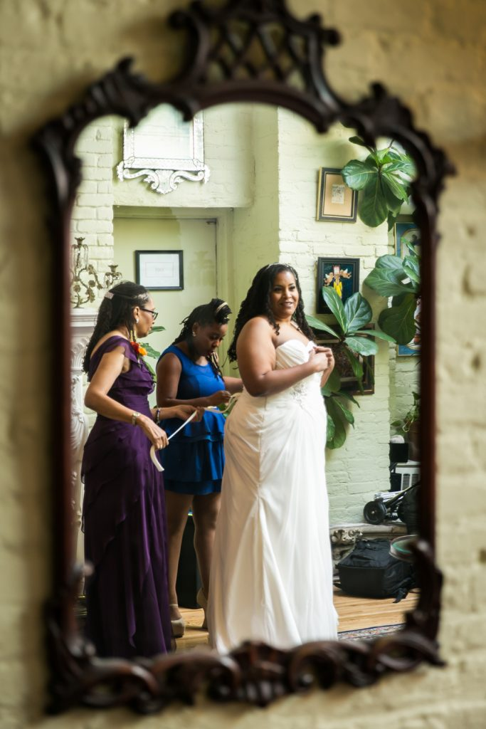 Reflection of bride in mirror getting into dress