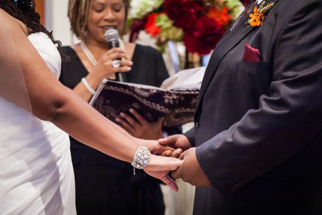 Close up on bride and groom holding hands during Alger House wedding ceremony
