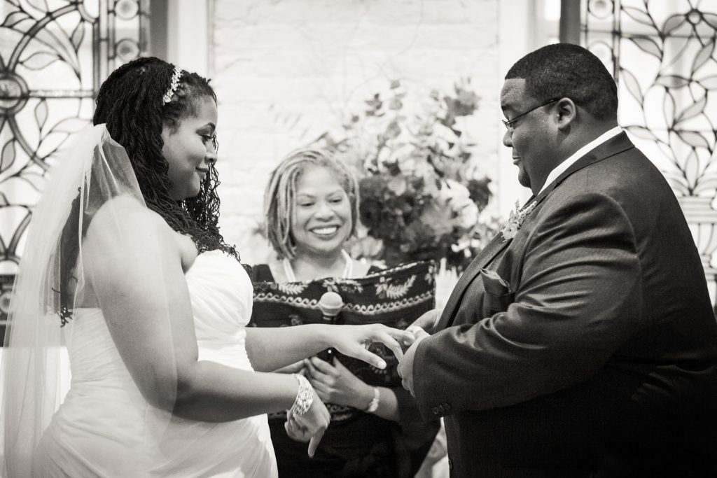 Black and white photo of groom putting wedding ring on bride