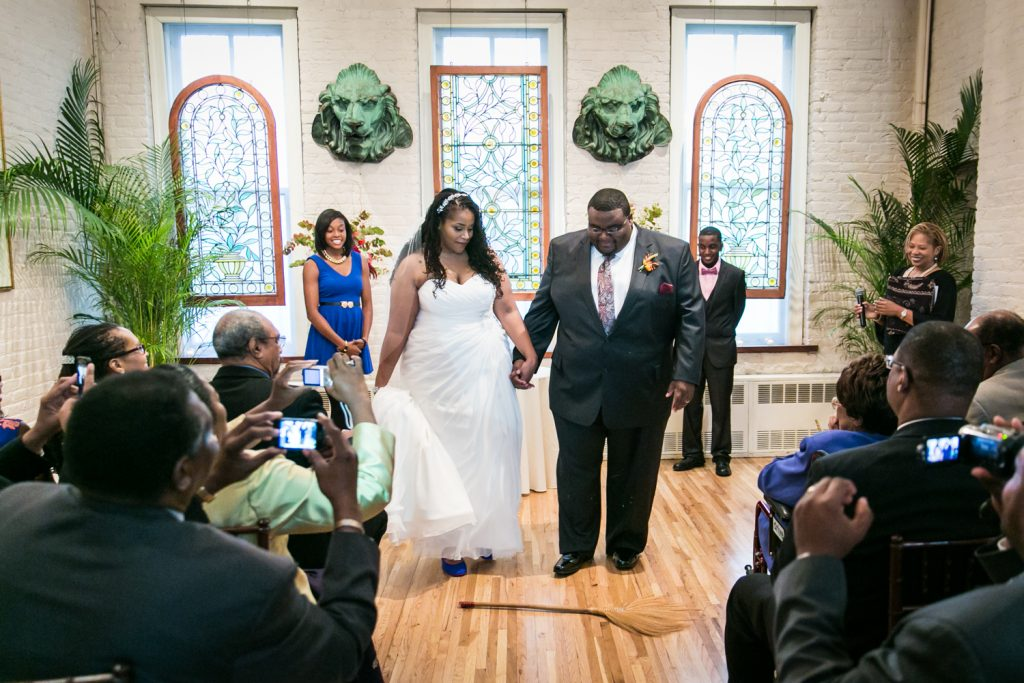 Alger House wedding portraits of bride and groom jumping the broom during ceremony