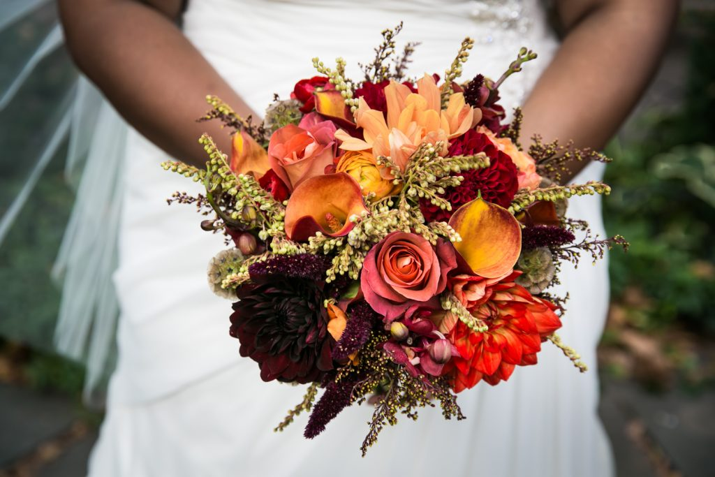 Close up on bride holding bouquet with orange, red, and yellow flowers