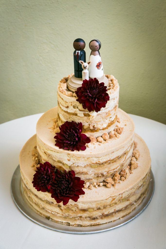 Momofuku milk wedding cake with brown icing, red flowers, and African American toppers