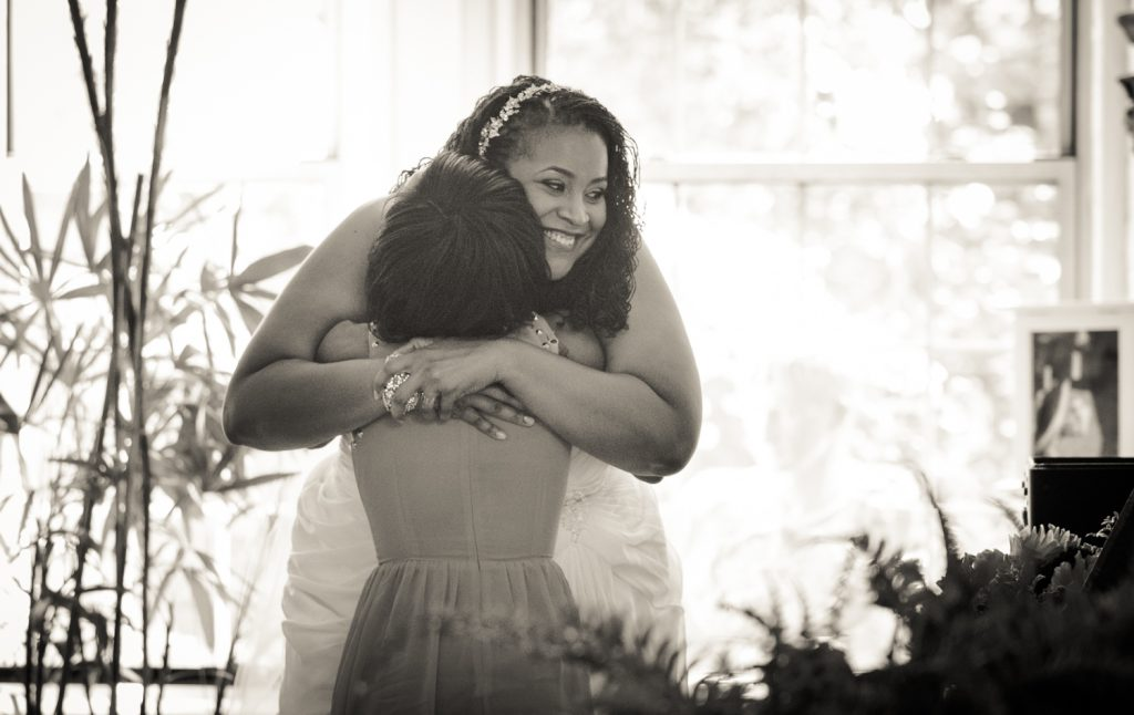 Black and white photo of bride hugging guest
