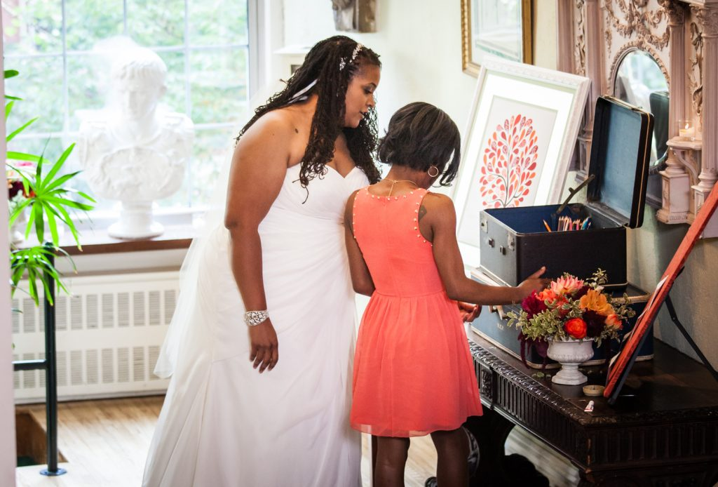Alger House wedding portraits of guest showing showing items to guest in orange dress