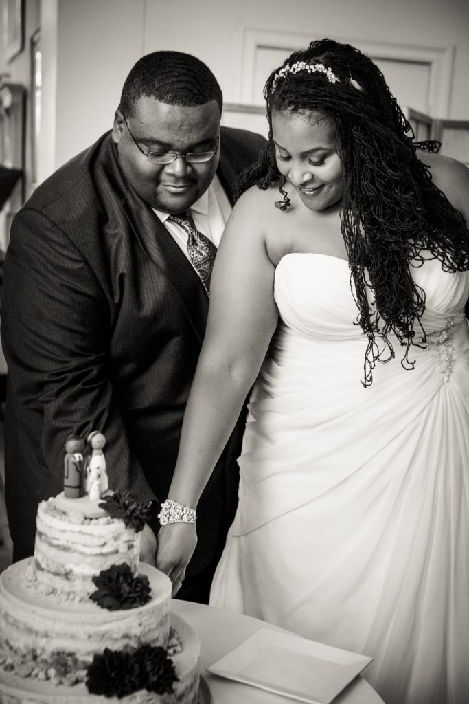 Black and white photo of bride and groom cutting wedding cake