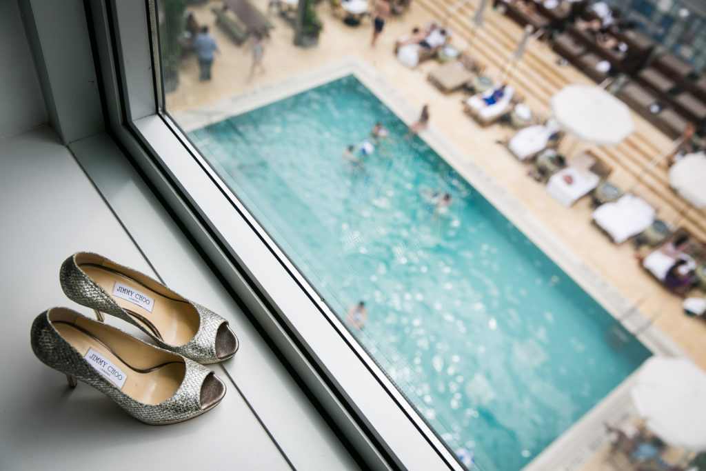 Jimmy Choo silver heels on windowsill with view of hotel pool below