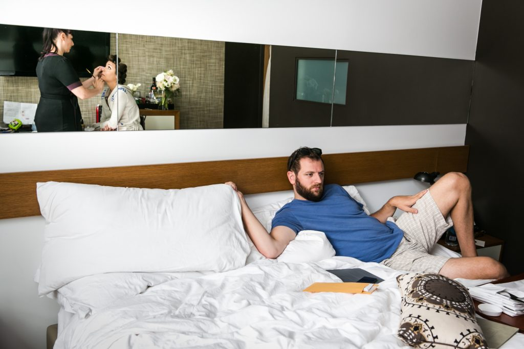 Groom lounging in bed with reflection of bride having makeup applied