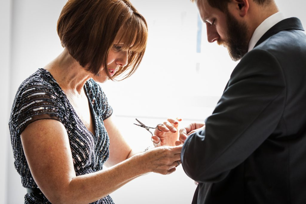 Close up of woman cutting strings off groom's sleeve