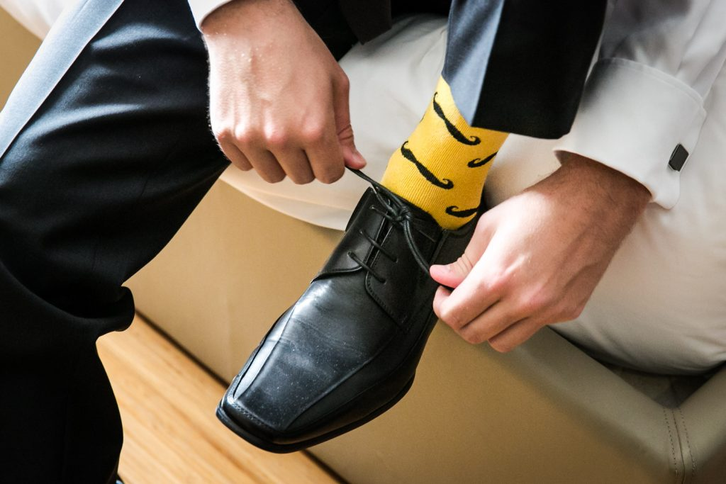 Close up of groom tying black shoe and wearing yellow socks with mustaches