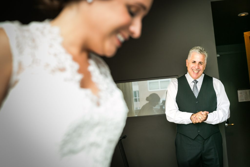 Father of bride watching as bride gets ready in hotel room