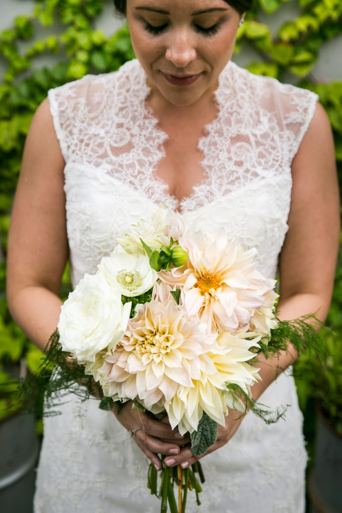 Bride looking down at bouquet at a Brooklyn Winery wedding