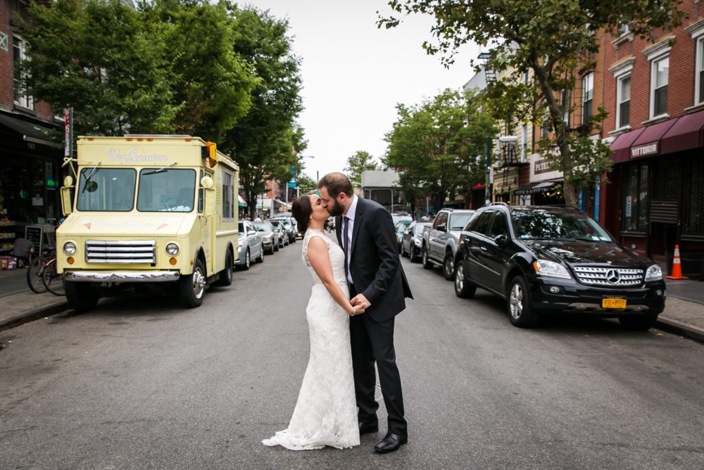 Bride and groom kissing in the middle of a street in Williamsburg