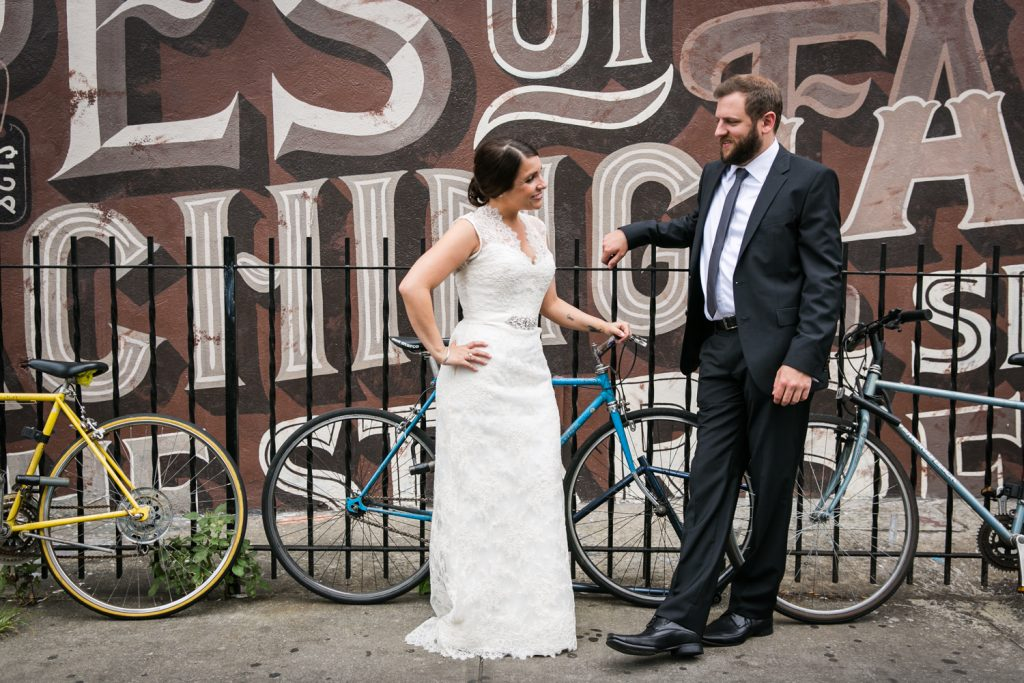 Bride and groom leaning against fence in Williamsburg at a Brooklyn Winery wedding
