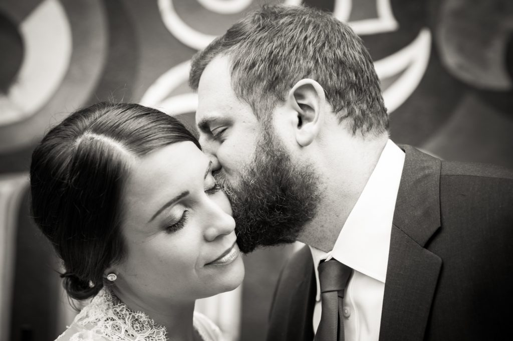 Black and white photo of groom kissing bride's cheek