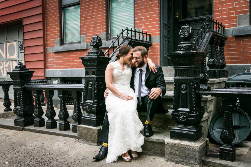 Bride sitting on groom's lap on brownstone staircase in Brooklyn