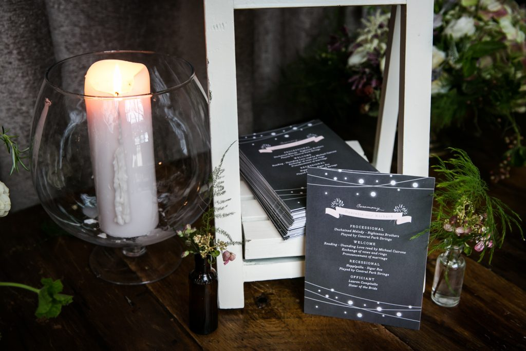 Wedding program and lit candle at a Brooklyn Winery wedding