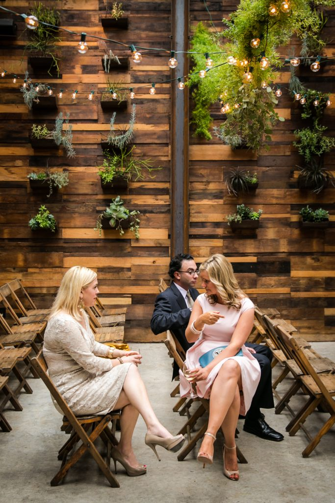 Three seated guests waiting for ceremony to begin at a Brooklyn Winery wedding