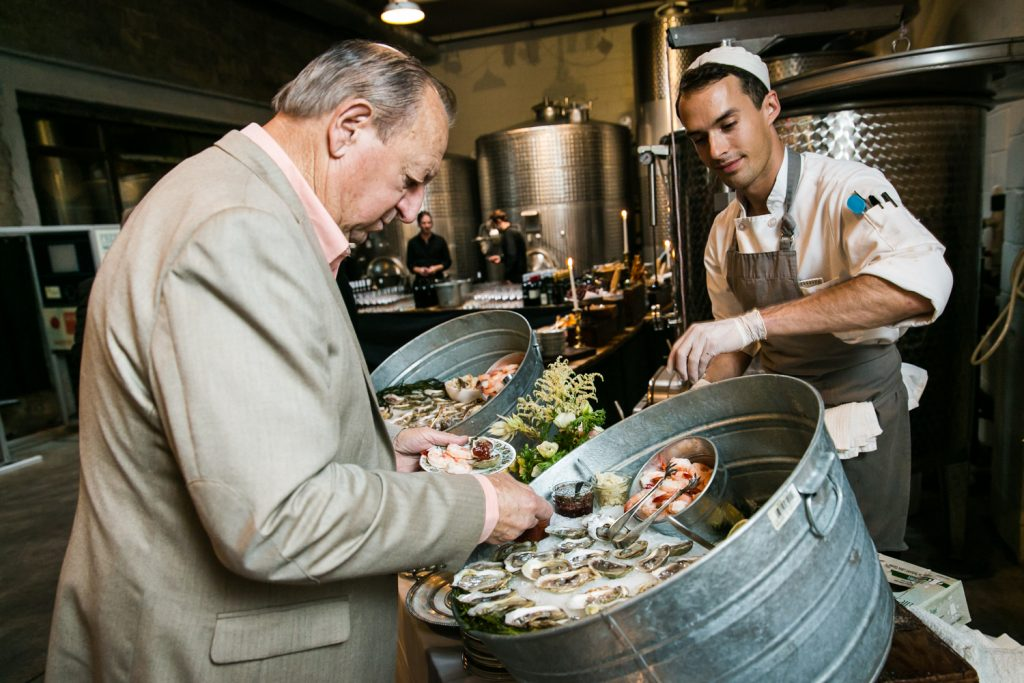 Guest selecting oyster from a buffet at a Brooklyn Winery wedding