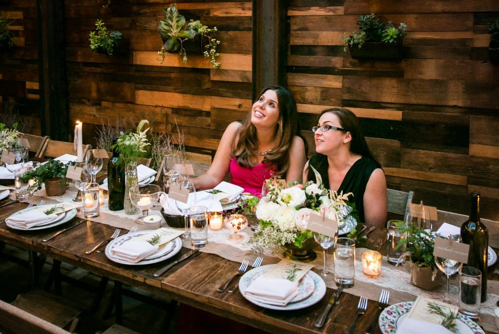 Two guests seated at wooden table at a Brooklyn Winery wedding