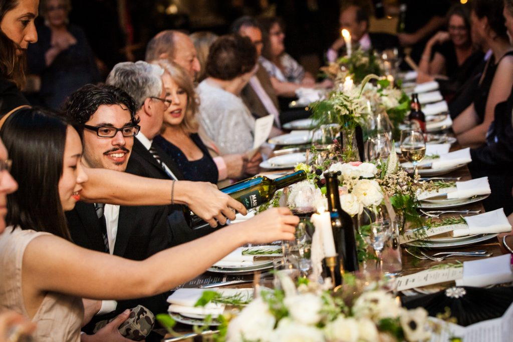 Waitress pouring wine for table of guests at a Brooklyn Winery wedding