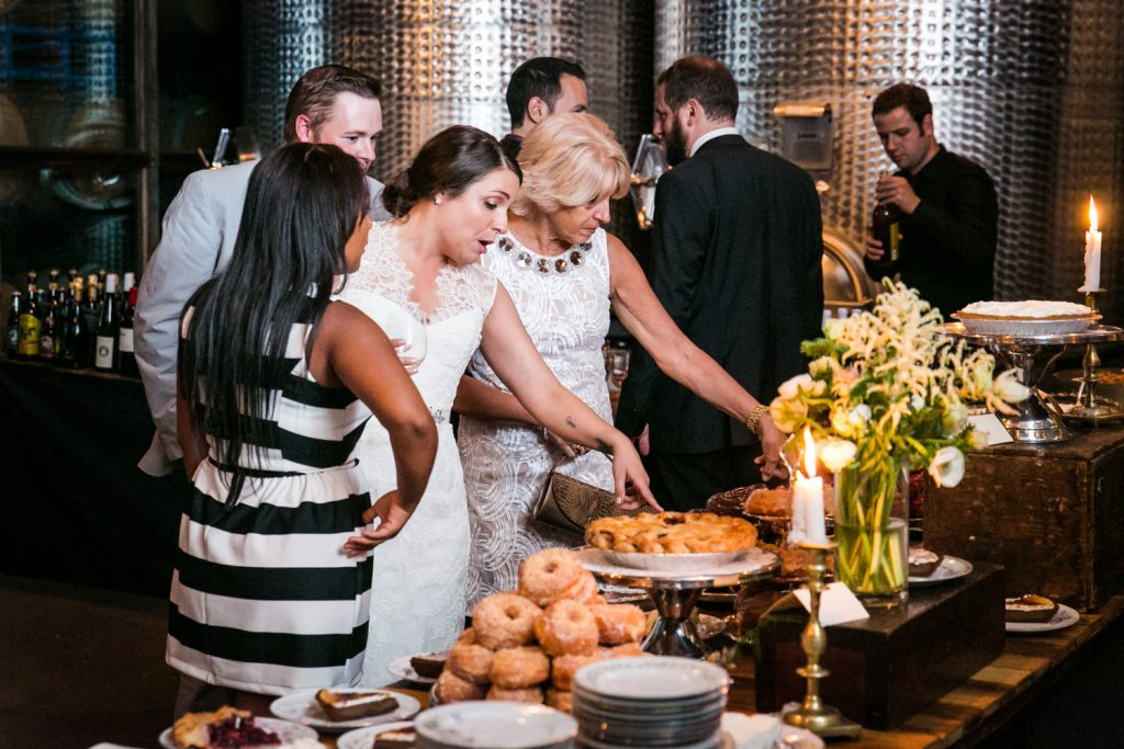 Bride pointing out dessert buffet to guests at a Brooklyn Winery wedding