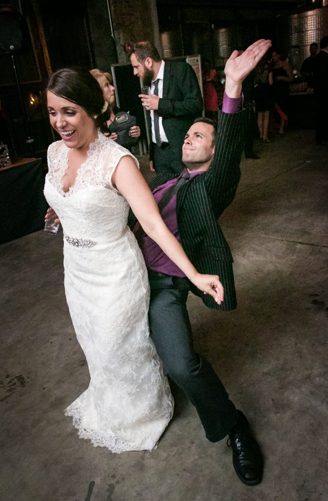 Guest dancing behind bride with hands in the air at a Brooklyn Winery wedding