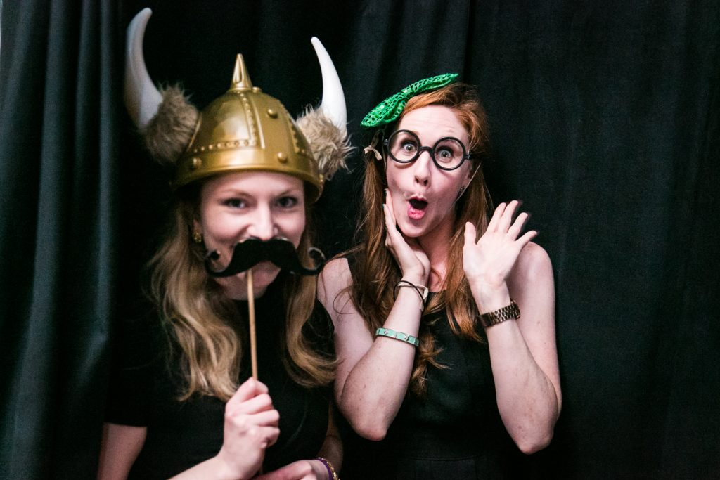 Two guests wearing props at a photobooth