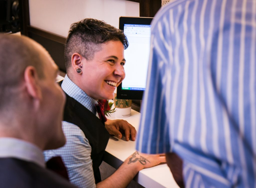 Groom at front desk laughing before a NYC LGBTQ City Hall wedding