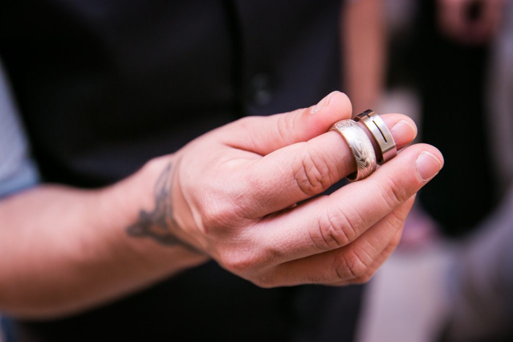 Groom's hand holding two wedding rings before a NYC LGBTQ City Hall wedding