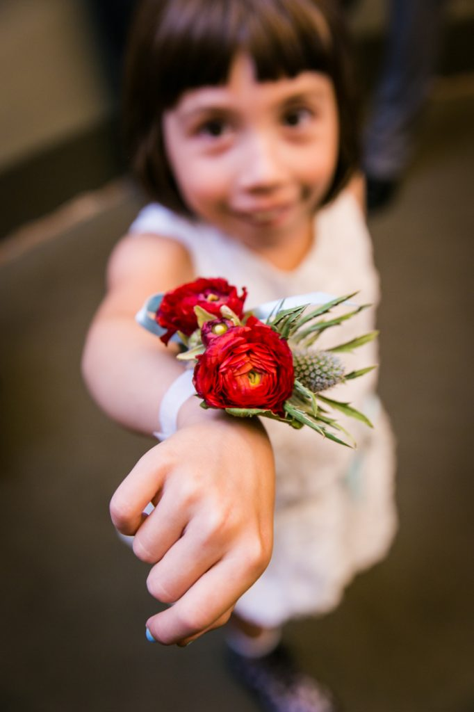 Little girl showing red flower wrist corsage before a NYC LGBTQ City Hall wedding