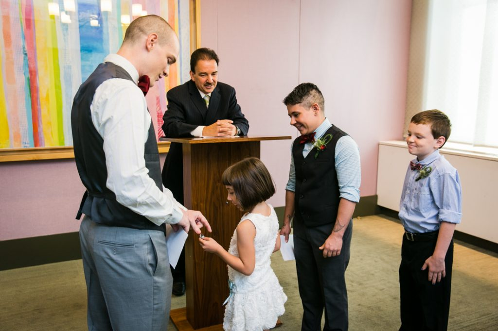 Little girl handing ring to groom during a NYC LGBTQ City Hall wedding