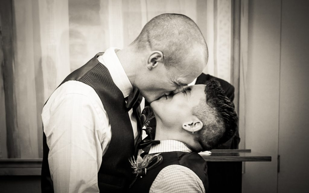 Black and white photo of two grooms kissing during a NYC LGBTQ City Hall wedding