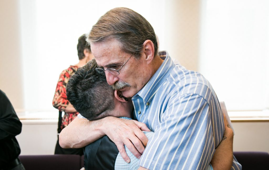 Father hugging groom after a NYC LGBTQ City Hall wedding ceremony