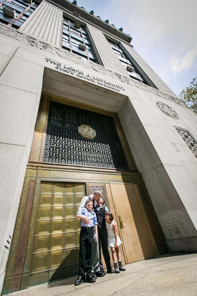 Two grooms and children outside bronze doors after a NYC LGBTQ City Hall wedding