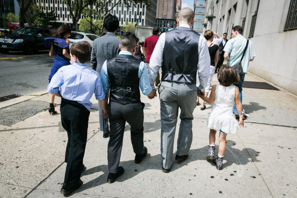Two grooms walking down sidewalk with children after a NYC LGBTQ City Hall wedding