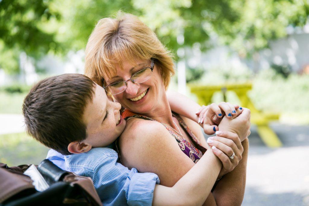 Little boy giving grandmother a hug in Gantry Plaza State Park